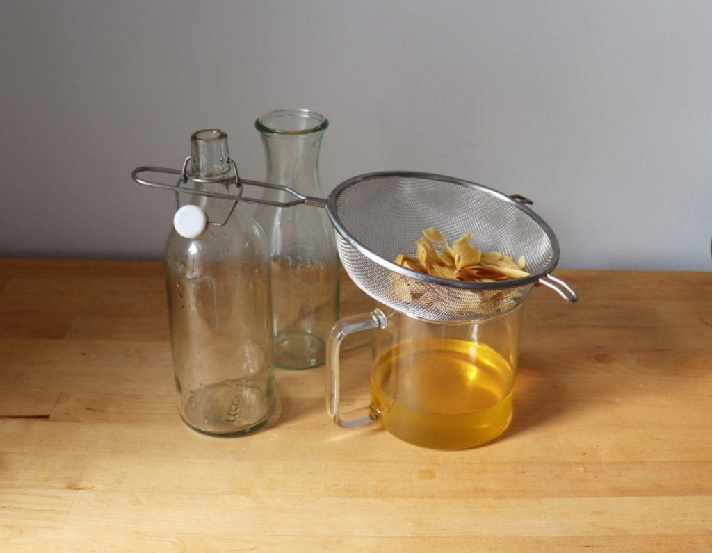 Zitronenschalen mit Weingeist durch ein Sieb gießen
