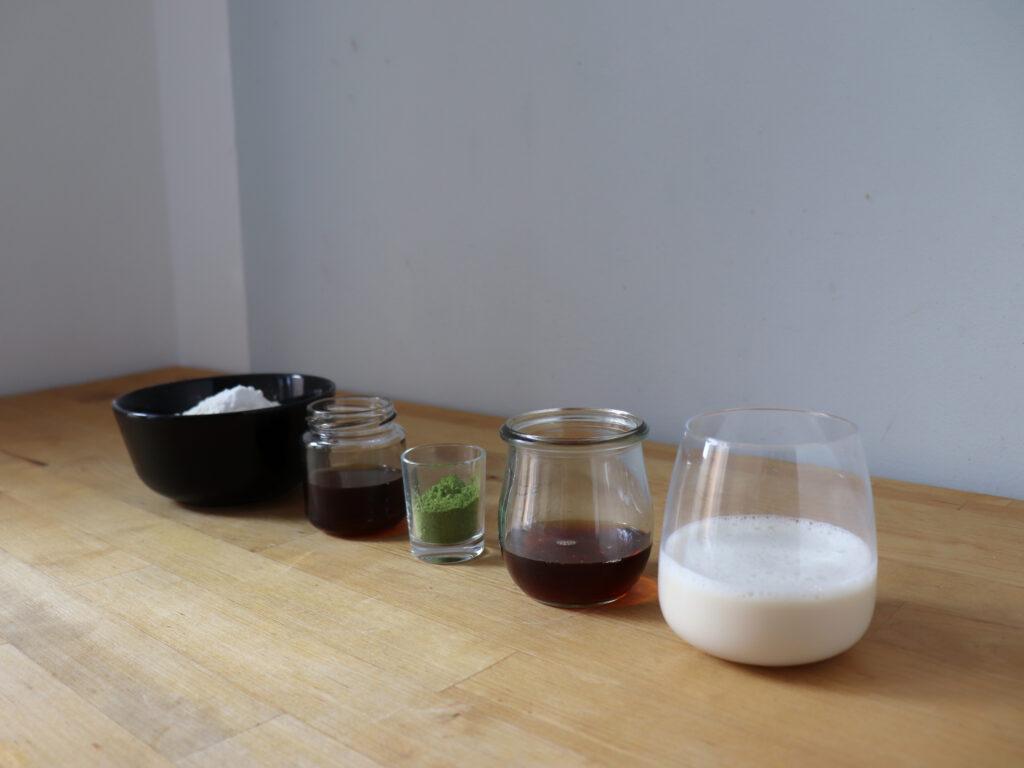 Mehl, Hafermilch, Sesamöl, Matcha Pulver, Ahornsirup und Backpulver