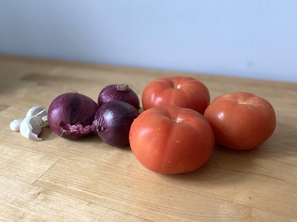 Frische Fleischtomaten, rote Zwiebeln, Knoblauchzehen